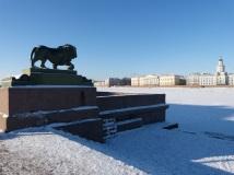 """Löwenfigur am Neva-Ufer, auf der anderen Seite des Flusses steht rechts das älteste Museum der Stadt, die """"Kunstkammer""""."""